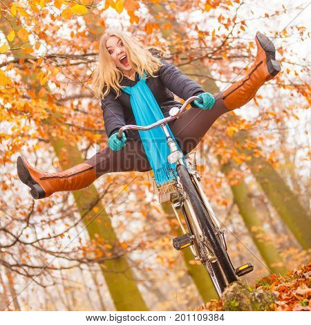 Happy carefree active woman having fun riding bike bicycle in fall autumn park. Crazy young girl relaxing. Healthy lifestyle and recreation leisure activity.