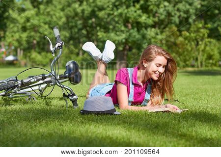 Attractive young woman smiling joyfully reading a book lying on the grass at the local park her bicycle on the background cyclist active lifestyle hipster positivity reader hobby travel summer concept.