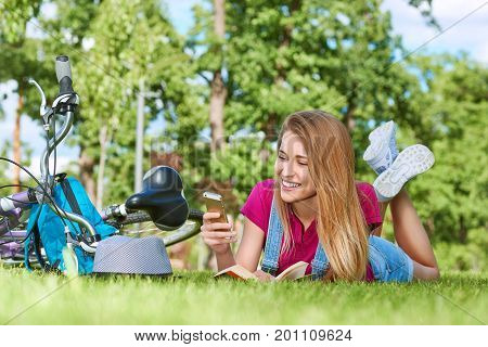 Happy young woman lying on the grass at the park after cycling smiling joyfully using her smart phone mobility gadget device technology carrier messaging communication leisure lifestyle.