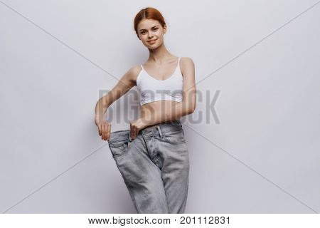 Beautiful young woman on a light background, leanness, diet, weight loss, success, progress.