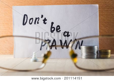 Concept of poverty on a wooden background pawn coins look through eye glasses