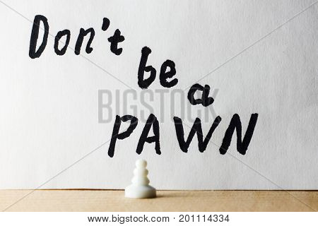 Chess figure symbolizing low status on the background of the inscription do not be a pawn in English