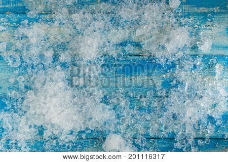 Crushed Ice Cubes On Vintage Blue Wooden Table. Top View