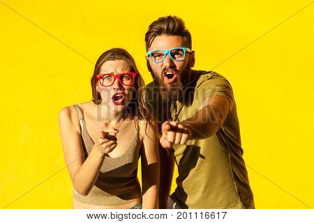Hey you! Young adult bearded man and cute brunette pointing fingers and looking at camera. On yellow background. Indoor studio shot