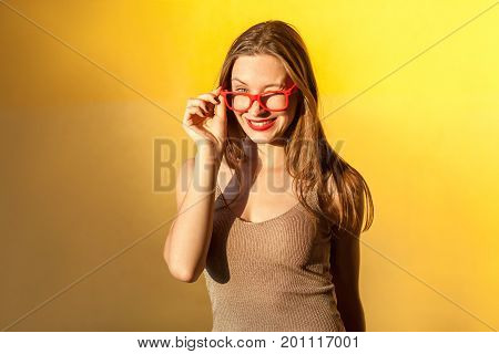 Sunglasses. Playfully girl wink at camera and toothy smile. Isolated on yellow background studio shot