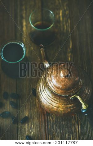 Oriental Middle Eastern vintage copper hummered tea pot, black tea in traditional tulip glasses and black raisins over rustic wooden background, selective focus, vertical composition