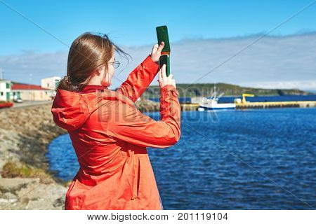 woman traveler in warm clothing take a photo of ocean and ship in Iceland. Travel to Iceland, West Fjords