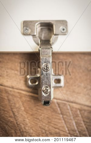 Door hinges at the cupboard on a wooden background Vertical frame