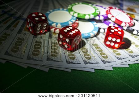 Stack of Poker chips with dice rolls on a dollar bills Money. Poker table at the casino. Poker game concept. Playing a game with dice. Casino dice rolls. Concept for business risk. chance good luck