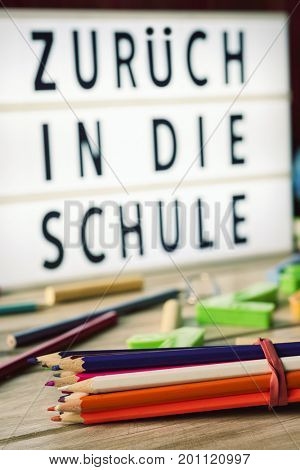 closeup of a bunch of pencils and some chalks of different colors and a lightbox in the background with the text zuruck in die schule, back to school in german