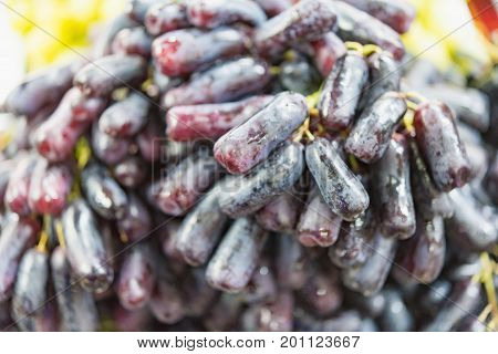 Extra jumbo size of black seedless Moon Drops grape or Witch Fingers grape for sale at the fruit market Selective focus on black seedless Moon Drop grapes
