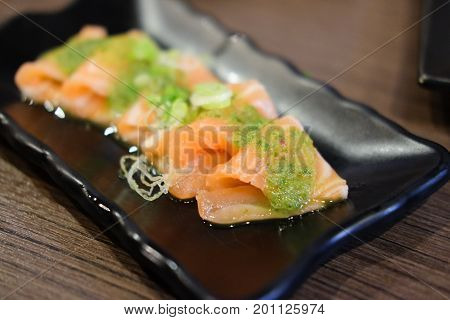 Japanese fusion food fresh salmon fish seafood sashimi mix with hot spicy chili sour lemon lime juice in Thai style menu.