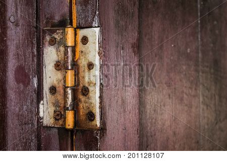 A rust hinge at the old wooden door. Protect Anti-theft Protection.