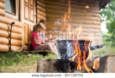 The family cooks food on open fire.