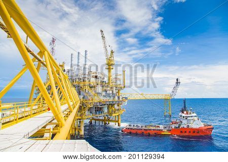 Oil and gas central processing platform construction crane loading cargo between platform and supply boat.