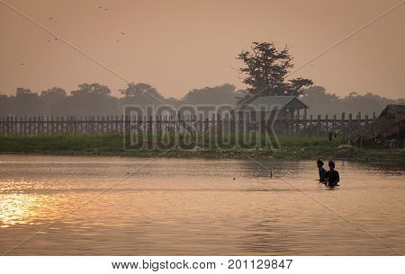 Mandalay Myanmar - May 1, 2016. View of U Bein Bridge at sunrise in Mandalay Myanmar. The beautiful U Bein bridge is easily one of Myanmar most photographed and iconic sites.
