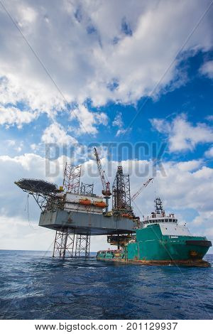 Ofshore oil and gas drilling at the gulf of Thailand Construction crane lifting and loading cargo to supply boat.