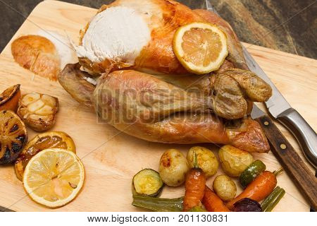 Lemon and garlic chicken Homemade Lemon and garlic Whole Chicken on a cutting board with vegetables being carved