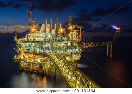 Offshore oil and gas industry in the gulf of Thailand Oil and Gas central processing platform and flare platform in twilight scene.