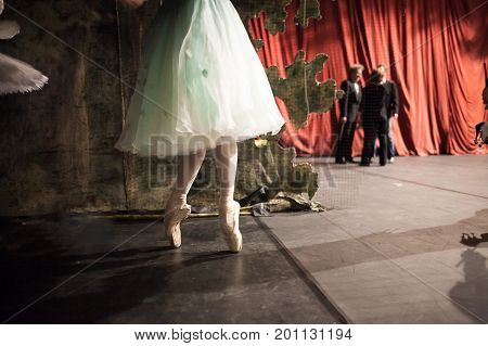 backstage, dramatic art, strength concept. small feet of weightless ballerina wearing dress with tulle skirt of turquoise color, she is rehearsing in the wings, doing exercises on tiptoe - en pointe