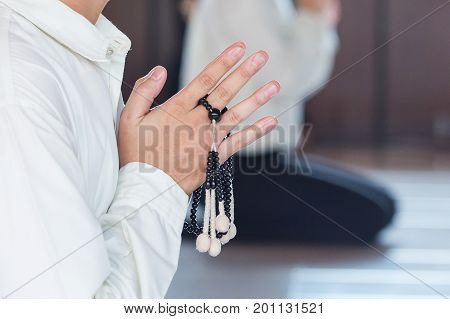 Prayer and holding prayer book and jutsu beads in japanese buddhist nichiren or shinto culture religion