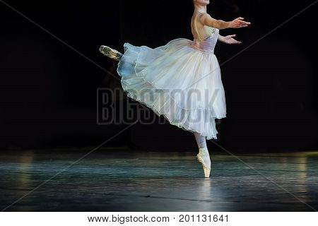 entertainment, art, choreography concept. gorgeous graceful ballerina dressed in blinding white ball gown dancing solo part all alone on the stage of the theater
