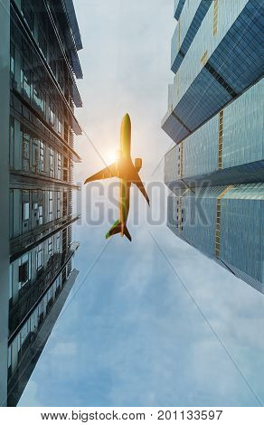 Airplane flying over city buildings high-rise business skyscrapers. Tourism transport transportation travel by airplane. Airplane transportation in center. City surround airplane transportation.
