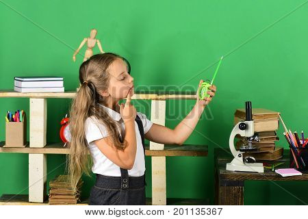 Kid And School Supplies On Green Background. Girl Holds Clock
