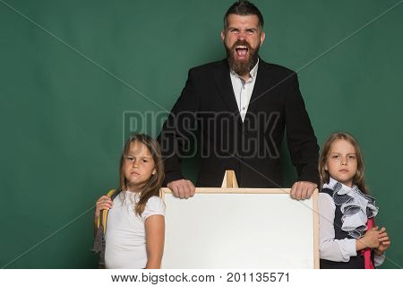 Man With Beard And Angry Face Stands Near Children