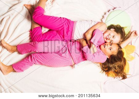 Children With Smiling Faces Lie On Pink Background And Hug