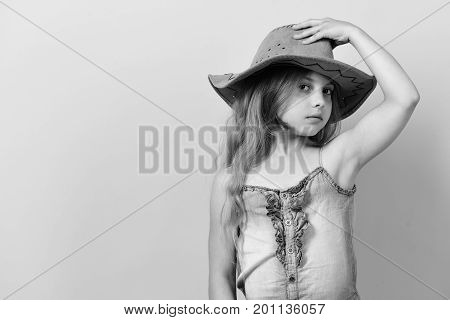 Kid with interested face and long fair hair wears jeans dress. Girl in fancy outfit holds cowboy hat. Fashion and casual style concept. Little lady in stylish clothes on pink background copy space