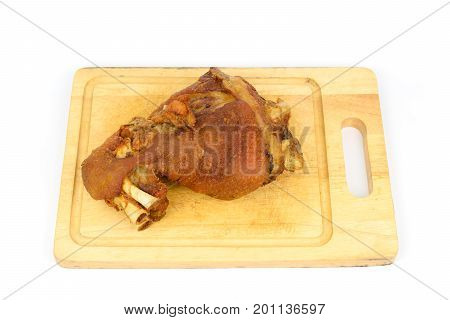 Schweinshaxe (german crispy pork knuckle) on a cutting board isolated white background.