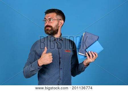 Notebooks In Blue Color In Guys Hand On Blue Background