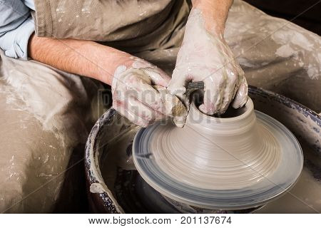 pottery, workshop, ceramics art concept - closeup on working potter's wheel with raw fireclay and man's hands, male fingers sculpt new utensil with a sponge and water, top view