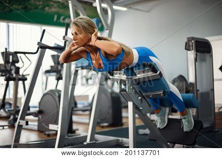 Athletic young woman doing hyperextension in the gym. Woman flexing back and abdominal muscles on bench