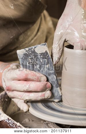 pottery, workshop, ceramics art concept - closeup on male fingers sculpt new utensil with a tools and water, man's hands working with potter's wheel and raw fire clay, close view, vertical