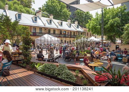 SYDNEY,NSW,AUSTRALIA-NOVEMBER 20,2016: People eating lunch at the Rocks Centre with musical group and local architecture by The Rocks Markets in Sydney, Australia.