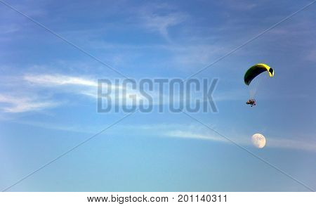 Paraglider in the sky flies over the moon