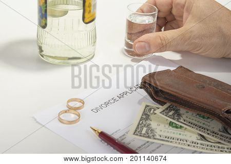 Unhappy man drinking spirit beacause filling up divorce application
