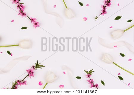 valentine day, spring, anniversary concept. on white desk there are magnificent tender flowers, creamy tulips, flowered brunches of cherrytree and ribbons. with negative space for text in the center