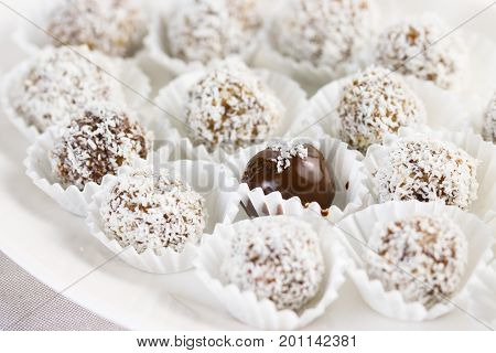 Date and almond pralines in ground coconut and one covered in chocolate