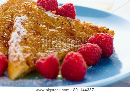 Close up on french toast with raspberries and honey. Selective focus shallow depth of field