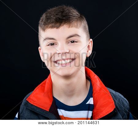 Close up emotional portrait of caucasian teen boy. Headshot of handsome guy. Funny cut teenager on black background. Smiling child looking at camera.