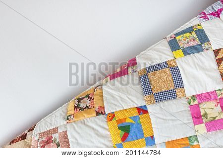 coziness, vintage, retro concept. part of quilled scrappy blanket with brigth-colored ornament represented by yellow, blue and pink squares falls off gradient from sofa