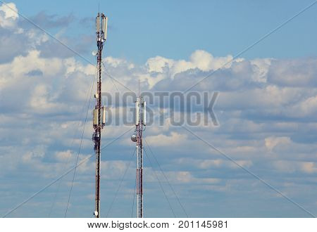 Two towers of cellular communication on the background of a blue cloudy sky.