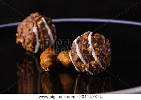 Nut and chocolate praline on elegant black plate