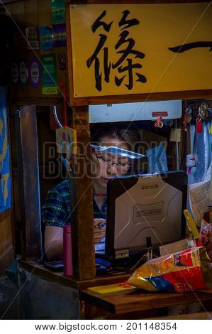 TOKYO, JAPAN JUNE 28 - 2017: Unidentified woman working in a coputer in the Fish Market Tsukiji wholesale in Tokyo Japan, Tsukiji Market is the biggest wholesale fish and seafood market in the world.