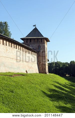 brick wall tower 11 century building the Novgorod Kremlin a castle a moat of grass the sky