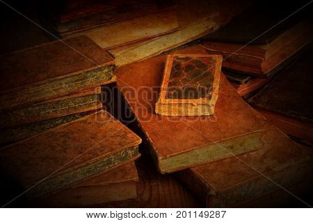 Vintage, antiquarian books pile on wooden surface in warm light