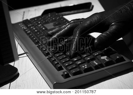 Hand in black glove types on keyboard. Scammers on the Internet